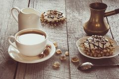 White cup of coffee with milk, white milk jug, brown sugar and homemade waffle with whipped cream with decor on top. Tasty breakfa Stock Photo