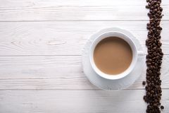White cup of coffee with milk or tea with milk on white wooden background decorated with coffee beans. Copy space stock photo