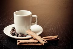 White cup with coffee near coffee beans over wood table Stock Image