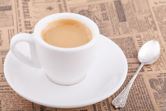 White cup of coffee on newspaper. White cup of coffee with spoon on newspaper Royalty Free Stock Image
