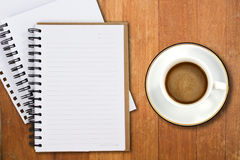 White cup of coffee and notebooks. On wood table Stock Images