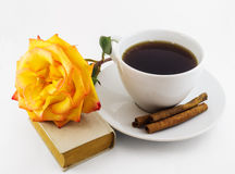 White cup of coffee, old book and yellow rose on white background Royalty Free Stock Images