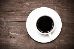 White cup of coffee on old wooden table. Toned Royalty Free Stock Photos