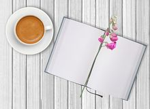 White cup of coffee and opened blank notebook with flower Royalty Free Stock Photos