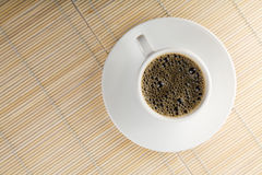 White cup of coffee over bamboo background Stock Images