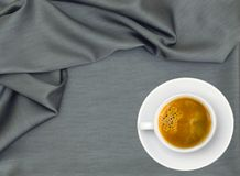 White cup of coffee over grey cloth Royalty Free Stock Images