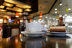 White cup of coffee and piece of cake in coffee shop Stock Photography