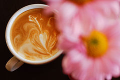 White cup of coffee with pink flower Royalty Free Stock Photography