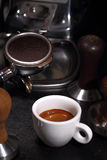 White cup of coffee and portafilter of an espresso machine Royalty Free Stock Photography