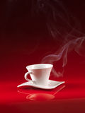 White cup of coffee on red background Stock Images