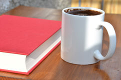 White cup of coffee and red book on brown wooden desk in sunshine Stock Photography