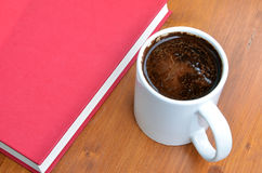 White cup of coffee and red book on brown wooden desk in sunshine Royalty Free Stock Photo