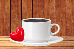White cup of coffee and red heart on wooden table over wooden pl Royalty Free Stock Photos