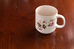 White cup of coffee with rose screen. On wooden table stock photography