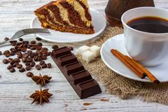 A white cup with coffee on sacking and a piece of amazing chocolate cake on a plate with a fork. A chocolate bar, coffee beans, an Stock Image