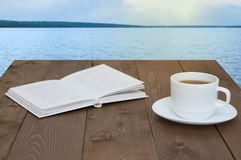 White cup with coffee on a saucer and a book. On wooden brown background. View of the sea stock images