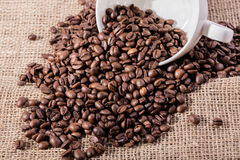 White cup with coffee seeds on jute bag Stock Image