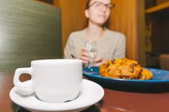 Cup of coffee and blue plate with raisin cookies royalty free stock photos