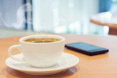 White cup of coffee with smartphone on wood table. stock images