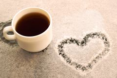 White cup with coffee and heart on the snow. White cup of coffee on a snow covered table. Figure in the form of a heart. Romantic morning at the resort in the royalty free stock images