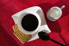 White cup with coffee on white square plate, with some cookies. stock photo
