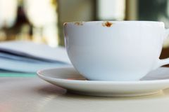 White cup of coffee on a table in cafe royalty free stock images