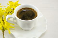White cup of coffee on a table decorated with flowers Royalty Free Stock Photo