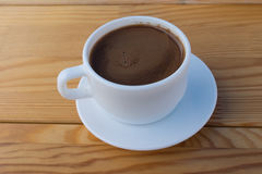 White Cup with coffee on the table. White coffee Cup on wooden table Stock Photo