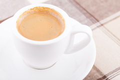 White cup of coffee on tablecloth. Close up white cup of coffee on tablecloth Stock Photography