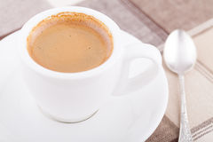 White cup of coffee on tablecloth. White cup of coffee with spoon on tablecloth Stock Image