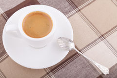 White cup of coffee on tablecloth Stock Photo