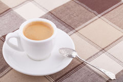 White cup of coffee on tablecloth. White cup of coffee with spoon on tablecloth Stock Photo