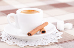 White cup of coffee on tablecloth. White cup of coffee with sugar and cinnamon on tablecloth Royalty Free Stock Image