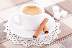 White cup of coffee on tablecloth. White cup of coffee with sugar and cinnamon on tablecloth Stock Image