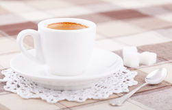 White cup of coffee on tablecloth. White cup of coffee with sugar and cinnamon on tablecloth Stock Images
