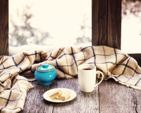 White cup of coffee or tea, blue pot on stylized wooden window s. White cup of coffee or tea, blue pot and woolen plaid located on stylized wooden window sill Royalty Free Stock Photo
