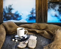 White cup of coffee or tea, lavender flowers, mittens and natur. Al gunny cloth located on stylized wooden window sill. Winter concept of comfort and relaxation Royalty Free Stock Images