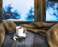 White cup of coffee or tea, lavender flowers and natural gunny c. Loth located on stylized wooden window sill. Winter concept of comfort and relaxation Royalty Free Stock Photography