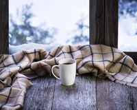 White cup of coffee or tea on stylized wooden window sill. White cup of coffee or tea and woolen plaid located on stylized wooden window sill. Winter concept of Royalty Free Stock Photo