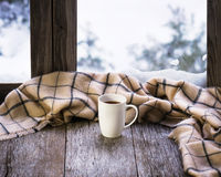 White cup of coffee or tea on stylized wooden window sill. White cup of coffee or tea and woolen plaid located on stylized wooden window sill. Winter concept of Stock Image
