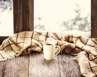 White cup of coffee or tea on stylized wooden window sill. White cup of coffee or tea and woolen plaid located on stylized wooden window sill. Winter concept of Stock Photo