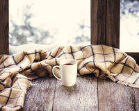 White cup of coffee or tea on stylized wooden window sill. White cup of coffee or tea and woolen plaid located on stylized wooden window sill. Winter concept of Stock Photos