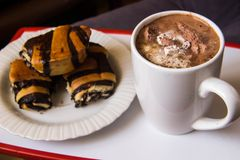 White cup with coffee on a tray with a plate with rolls with pop stock images