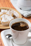 White cup of coffee with turkish delight in the background Royalty Free Stock Images