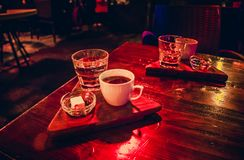A white cup of coffee with Turkish delight on the table at night royalty free stock photography
