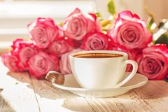 White cup of coffee for valentine or romantic morning with pink roses.  Royalty Free Stock Images