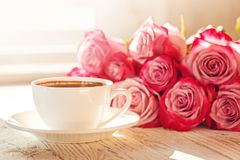 White cup of coffee for valentine or romantic morning with pink roses. White cup of coffee for valentine or romantic morning with pink roses Royalty Free Stock Images