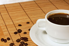 White cup of coffee on a wicker table cloth. White coffee cup and saucer with coffee beans is on the wicker table cloth Stock Images