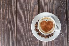 Cup of coffee on a wooden table, with cocoa powder forming a heart on the foam. White cup of coffee on a wooden table, with cocoa powder forming a heart on the stock photo