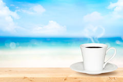 White cup of coffee on wooden table with defocused blue sea Stock Images